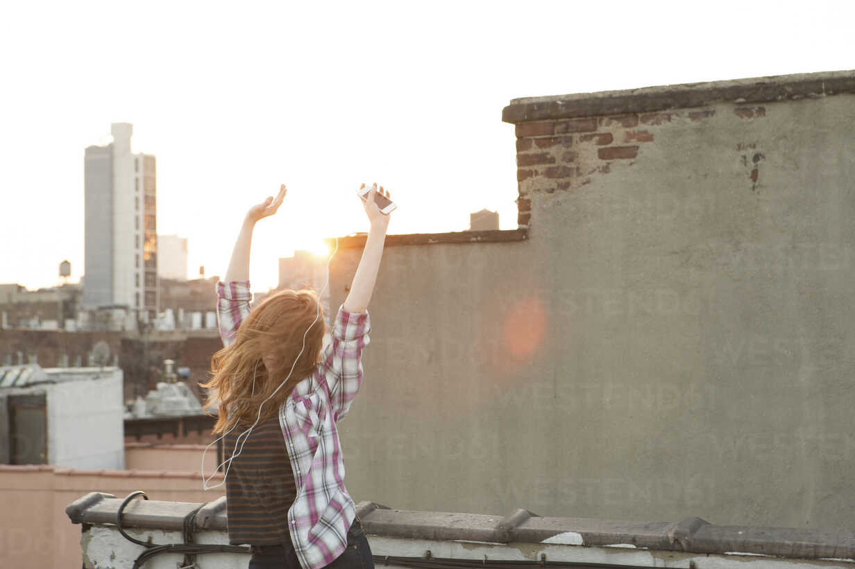 Young woman listening to music with arms raised on city rooftop - ISF00756 - Sean Murphy/Westend61
