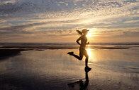 Woman running on beach at sunrise - ISF00909