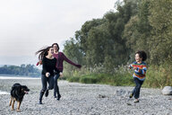Boy and young women running with dog along riverside, Calolziocorte, Lombardy, Italy - CUF01869
