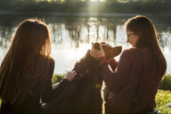 Two young women petting dog on river bank, Calolziocorte, Lombardy, Italy - CUF01872