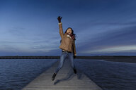 Young woman jumping on pier at dusk, Tarragona, Catalonia, Spain - CUF02013
