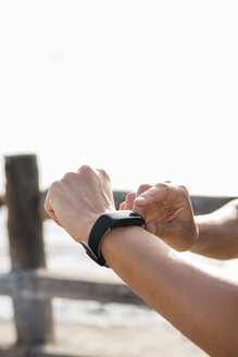Young woman training on sea waterfront looking at smartwatch, close up of hands - CUF02025