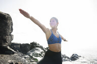 Young woman practicing yoga warrior pose on beach, Las Palmas, Canary Islands, Spain - CUF02031