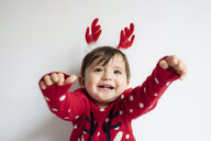 Portrait of happy baby girl with reindeer antlers headband at Christmas time - GEMF01940