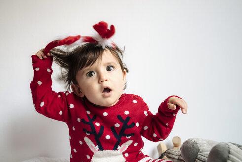 Portrait of disgusted baby girl pulling off reindeer antlers headband - GEMF01943