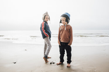 Portrait of two brothers, standing on beach, wearing knitted hats - CUF02099