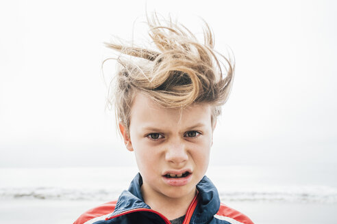 Portrait of boy on beach, messy hair, making face, close-up - CUF02108