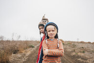 Portrait of two brothers, outdoors, wearing knitted hats, making faces - CUF02132
