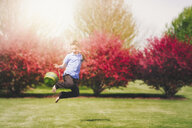 Boy outdoors, jumping in air, holding Easter basket - CUF02135