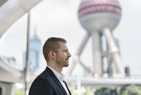 Young businessman gazing out at Shanghai financial centre, Shanghai, China - CUF02183