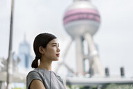 Young businesswoman looking out at Shanghai financial centre, Shanghai, China - CUF02186