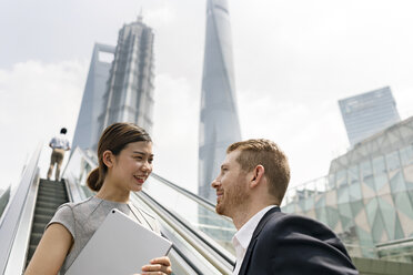 Young businessman and woman moving up escalator in Shanghai financial centre, Shanghai, China - CUF02192
