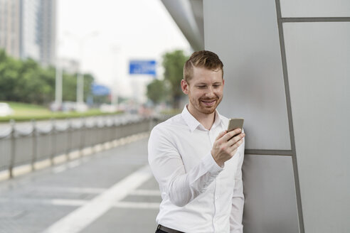 Young businessman looking at smartphone touchscreen in city, Shanghai, China - CUF02195