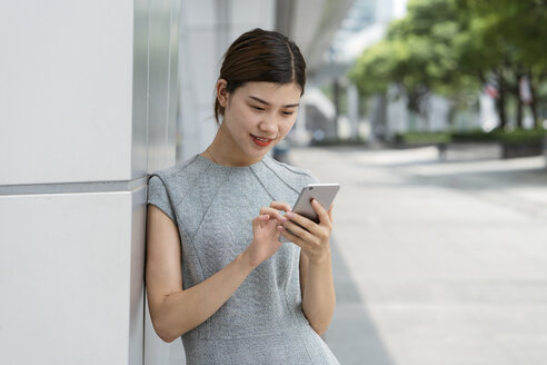 Young businesswoman using smartphone touchscreen in city, Shanghai, China - CUF02198