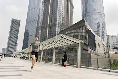 Young male runner running in Shanghai financial centre, Shanghai, China - CUF02201