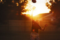 Boy practicing american football in garden reaching to catch ball mid air at sunset - CUF02204