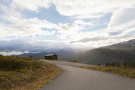 Sunlit rural road in mountain landscape, Jotunheimen National Park, Lom, Oppland, Norway - CUF02407