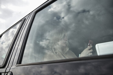 Young woman sitting in a car looking at cell phone - MMIF00004