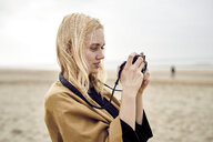 Blond young woman using camera on the beach - MMIF00016
