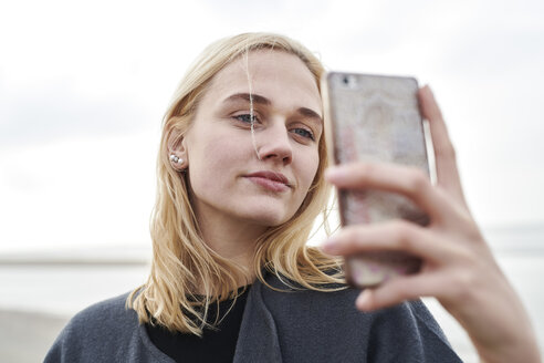 Portrait of blond young woman taking selfie with smartphone on the beach - MMIF00022
