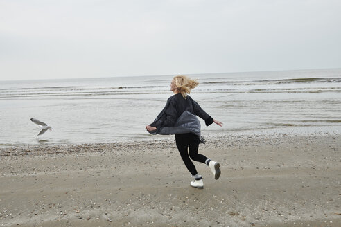 Netherlands, happy blond young woman running on the beach - MMIF00025