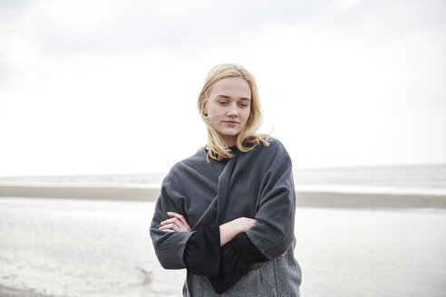Netherlands, portrait of blond young woman on the beach - MMIF00028