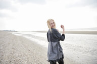 Netherlands, portrait of happy blond young woman  on the beach - MMIF00031