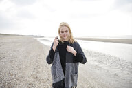 Netherlands, blond young woman wearing gray jacket on the beach - MMIF00034