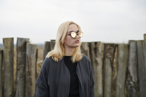 Portrait of blond young woman wearing mirrored sunglasses on the beach - MMIF00037