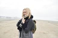 Portrait of blond young woman with backpack on the beach in winter - MMIF00040