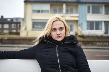 Netherlands, portrait of blond young woman sitting on bench in winter - MMIF00049