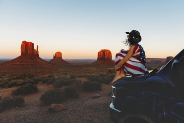 USA, Utah, Woman with United States of America flag enjoying the sunset in Monument Valley - GEMF01949