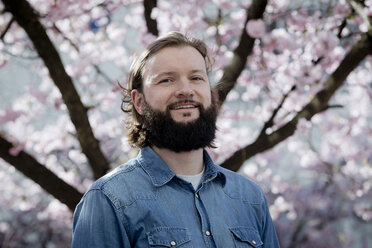 Portrait of bearded man in front of blossoming cherry tree - FLLF00029