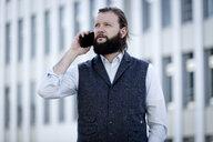 Portrait of bearded businessman on the phone wearing waistcoat - FLLF00035
