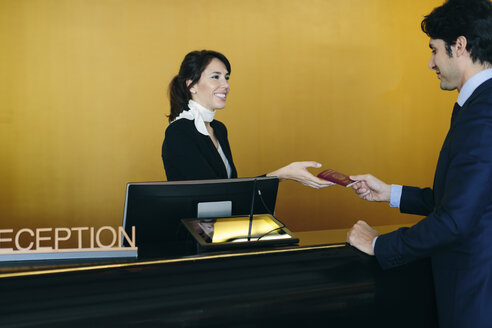 Businessman checking in at hotel reception - CUF02436