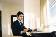 Businessman texting while using laptop by hotel room window - CUF02451