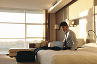 Businessman using laptop on bed of hotel bedroom - CUF02454