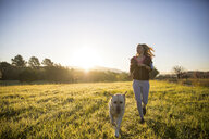 Young woman running across field, with pet dog - CUF02568