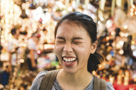 Tourist laughing in bazaar, Bangkok, Thailand - CUF02583