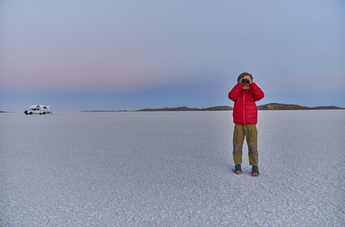 Young boy standing on salt flats, looking at view, recreational vehicle in background, Salar de Uyuni, Uyuni, Oruro, Bolivia, South America - CUF02613