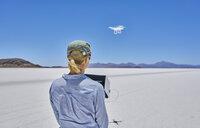 Woman on salt flats, flying drone, rear view, Salar de Uyuni, Uyuni, Oruro, Bolivia, South America - CUF02619