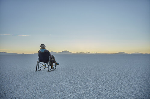 Woman sitting in camping chair, on salt flats, looking at view, Salar de Uyuni, Uyuni, Oruro, Bolivia, South America - CUF02622
