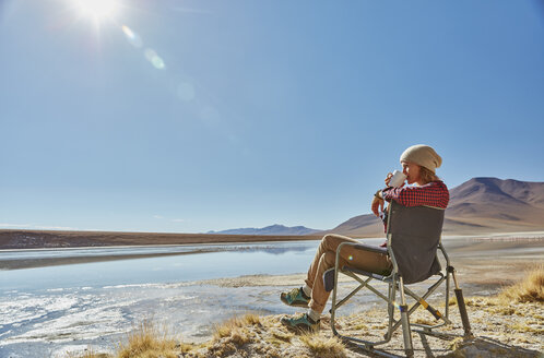 Woman sitting in camping chair, looking at view, Salar de Chalviri, Chalviri, Oruro, Bolivia, South America - CUF02625