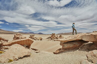 Woman standing on rock, looking at view, Villa Alota, Potosi, Bolivia, South America - CUF02628