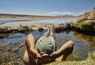 Man relaxing in water pool, rear view, Salar de Chiguana, Chiguana, Potosi, Bolivia, South America - CUF02631