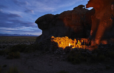Mother and sons, sitting beside camp fire at dusk, Oruro, Oruro, Bolivia, South America - CUF02634