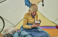Woman sitting in tent, eating food from bowl, Ventilla, La Paz, Bolivia, South America - CUF02643