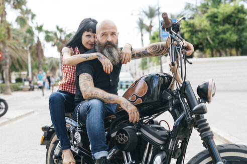 Mature hipster couple astride motorcycle, Valencia, Spain - CUF02694