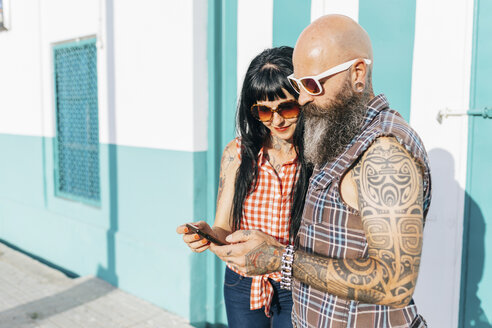 Mature hipster couple looking at smartphone on sidewalk - CUF02706