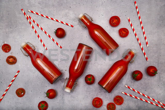Homemade tomato juice in swing top bottles, straws and tomatoes on grey ground - RTBF01265